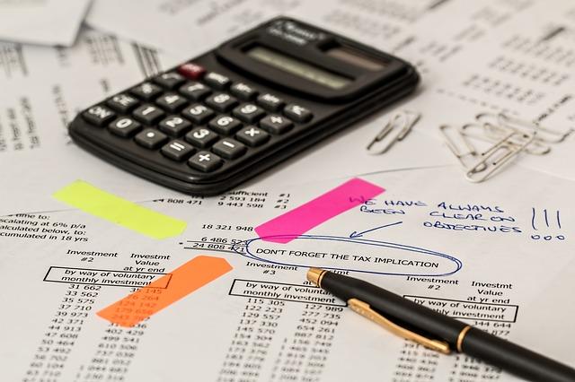 Das Bild zeigt einen Taschenrechner, einen Stift und Papier.