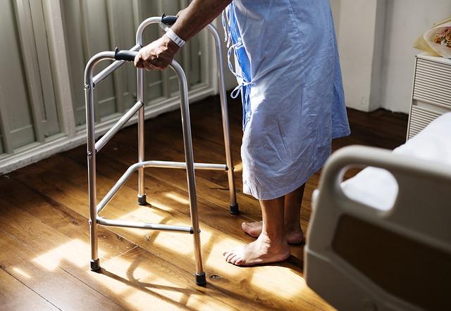 Das Bild zeigt eine Person mit einem Gehgestell vor einem Bett.