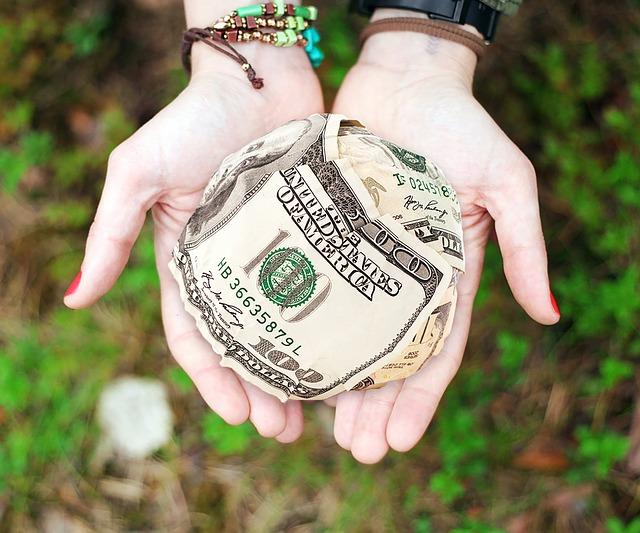 Zwei Hände halten einen Ball Geldscheine